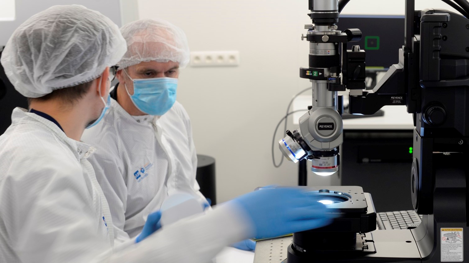 two photonics engineers working in a clean room wearing protective equipment